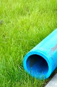 Harmless polyethylene water pipes on a green grass