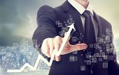 stock photo of graphs  - Businessman Touching a Graph Indicating Growth on City Background - JPG