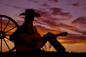 picture of cowgirls  - A cowgirl sitting up against a wagon wheel playing her guitar with the sunset behind her - JPG