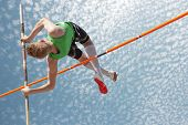 stock photo of pole  - Young athletes pole vault seems to reach the sky - JPG
