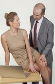 pic of groping  - Suave balding businessman groping his secretary on the leg and leaning over her as she sits on a table in the office working on a laptop conceptual of unsolicited sexual harassment in the workplace - JPG