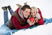 picture of blanket snow  - Woman and man are relaxing in winter snowy countryside - JPG