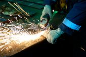 worker welding metal with sparks at factory