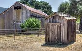 stock photo of outhouses  - Dilapidated and Abandoned Outhouse in the American West.