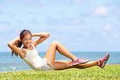 stock photo of stomach  - Exercising fitness woman doing sit ups outside during crossfit exercise training - JPG