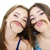 Portrait of a two teen girls have fun and make faces with moustache made of hair pigtail, isolated o