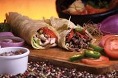 stock photo of mexican food  - this is a meat and chicken mexican burrito with red and green peppers  - JPG