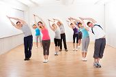 stock photo of stretching  - Large group of diverse people in a pilates class exercising in a gym doing core stretching - JPG
