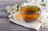 foto of jasmine  - Cup of tea with jasmine on table close - JPG