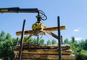 stock photo of logging truck  - forestry work yellow cutter loading the cut logs in pile on trailer - JPG