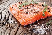 stock photo of wood pieces  - Salmon filet with spices on a wooden carving board - JPG