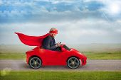 pic of superhero  - senior superhero with mask and cape driving a toy sports car - JPG