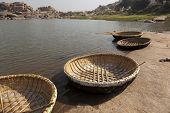 stock photo of stereotype  - Round stereotypic boats and hills with amazing stones at Hampi temple complex in India - JPG