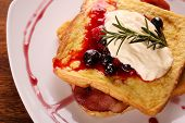 picture of french toast  - Delicious french toast with bacon syrup berries and cream on a white plate on a wooden table - JPG
