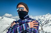 pic of rapper  - Portrait of young man hiding his face bandana and sunglasses jokingly shows steep gangster rapper man at ski resort in the background of mountains and blue sky - JPG