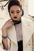 image of coat  - fashion outdoor photo of beautiful elegant lady wearing luxurious beige coat and silk scarf on her head - JPG