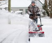picture of driveway  - Man clearing deep snow from residential driveway after heavy snowfall - JPG