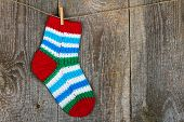 pic of clotheslines  - Colorful sock hanging on the clothesline on old wooden background - JPG