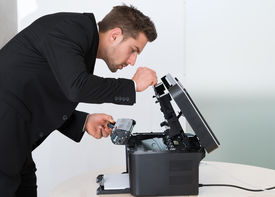 picture of cartridge  - Side view of young businessman fixing cartridge in photocopy machine at office - JPG