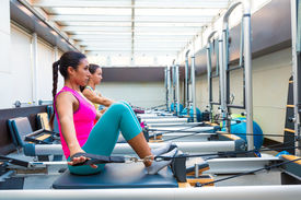 picture of pilates  - Pilates reformer workout exercises women at gym indoor - JPG