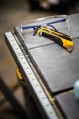 image of protective eyewear  - Protective Glasses and Utility Knife on a Table Saw - JPG