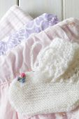 stock photo of booty  - New Baby Girl Clothes on a Table with Baby Booties At the Top  - JPG