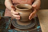 image of loam  - The hands of a potter creating an earthen jar on the circle close - JPG