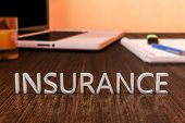 stock photo of insurance-policy  - Insurance - letters on wooden desk with laptop computer and a notebook. 3d render illustration. ** Note: Shallow depth of field - JPG