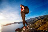 stock photo of vest  - Sports woman in red vest with backpack standing on the top of mountain on the sunset - JPG
