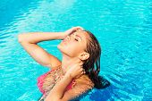 picture of woman bikini  - Side view of beautiful young woman in bikini adjusting her wet hair and keeping eyes closed while standing at the pool - JPG