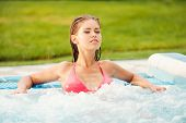 picture of hot-tub  - Attractive young woman in bikini relaxing in hot tub and keeping eyes closed - JPG