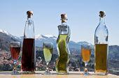 stock photo of liquor bottle  - photo of three bottles of liquor and glasses full - JPG