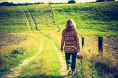 image of girl walking away  - Girl in sweater walking by rural grassy road in countryside landscape. Photo with vintage mood