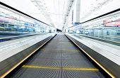 image of escalator  - symmetric moving blue escalator inside contemporary airport - JPG