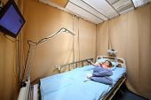 picture of ward  - Little girl lying on the bed with remote control in hand in a hospital ward - JPG