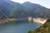 foto of arid  - Dam creating a lake with low water levels caused by an ongoing drought taken at the San Gabriel River - JPG