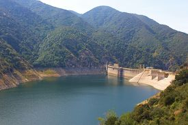 stock photo of drought  - Dam creating a lake with low water levels caused by an ongoing drought taken at the San Gabriel River - JPG