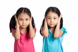 stock photo of identical twin girls  - Asian twins girls cover their ears isolated on white background - JPG