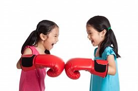 stock photo of identical twin girls  - Happy Asian twins girls with boxing gloves isolated on white background - JPG