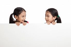 picture of identical twin girls  - Happy Asian twins girls behind white blank banner on white background - JPG
