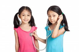 stock photo of identical twin girls  - Happy Asian twins girls with stethoscope isolated on white background  - JPG
