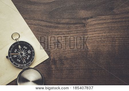 poster of traveling compass and old paper with copy space. traveling concept on the brown wooden table. traveling background. traveling directions.