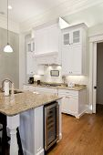 stock photo of opulence  - opulent white kitchen with granite countertops and wine fridge - JPG