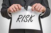Businessman Tearing Paper With Risk Word poster