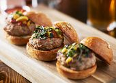 tow of three mini turkey burger sliders with brioche buns poster