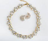 Diamonds Necklace A White Background. Stylish Necklace With Colorful Stones. A Round Gold Metal Neck poster