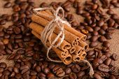 Coffee Beans And Cinnamon On A Background Of Burlap. Roasted Coffee Beans Background Close Up. Coffe poster