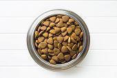 Dry kibble dog food in metal bowl. Top view. poster