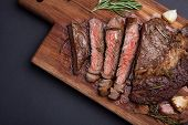 Grilled Rib-eye Steak Of Marble Beef Closeup With Spices On A Wooden Board. Juicy Steak Medium Slice poster