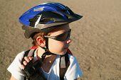 Постер, плакат: Девятилетний мальчик носить солнцезащитные очки шлем велосипеда и рюкзак приседает в Солнечный парк